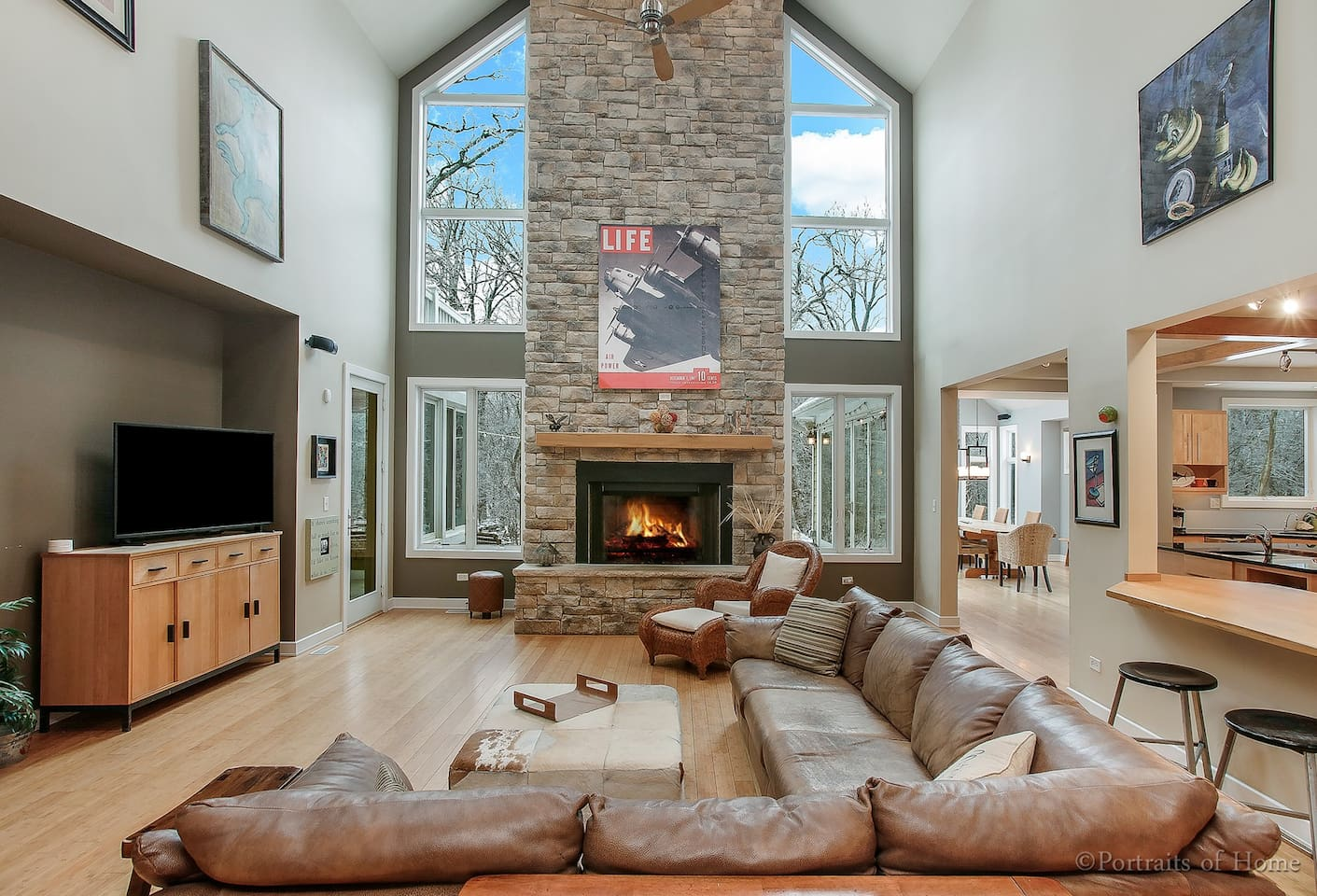 The Living Room flows into the Kitchen to the right, and the 3 seasons Dining Room behind the Kitchen. This is an open Floor Plan layout flooded with natural light! The floor to ceiling glazing overlooks the woods and backyard.