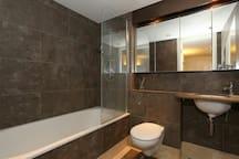 Luxurious spa ambience bathroom with soak-in bathtub, mood lighting and heated towel rails
