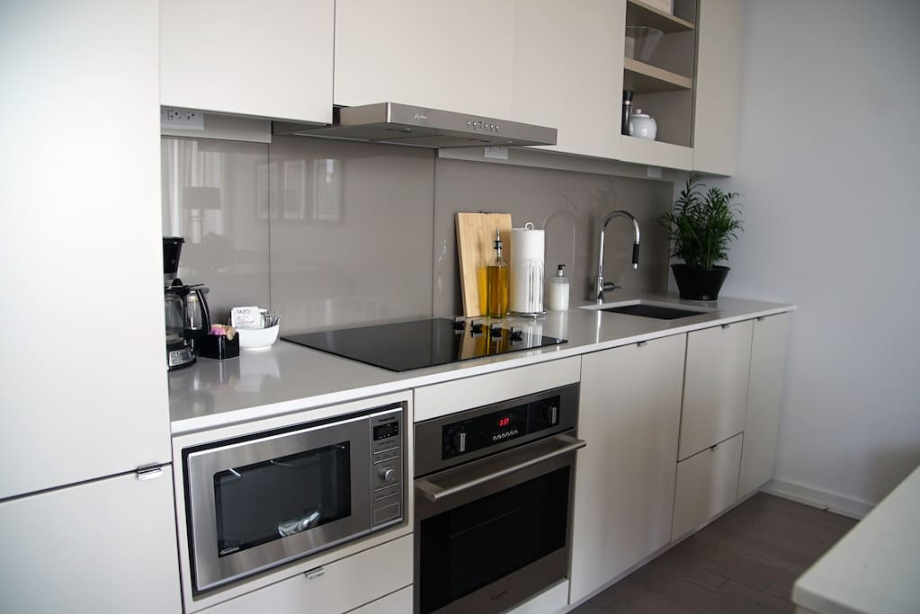Fully equipped kitchen with microwave, dishwasher, toaster, blender, coffee maker and snacks.