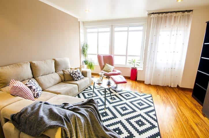 Gran salón con un espacioso sofá, sillón de masajes y smart TV.