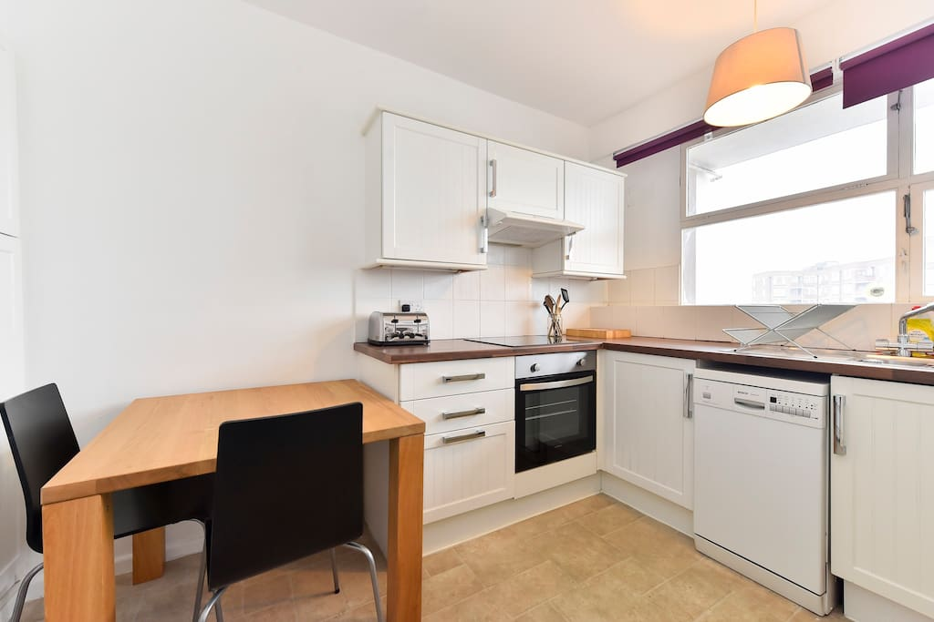 The kitchen contains a small table with two chairs, a washer-dryer, a dishwasher, oven and hob, microwave, fridge freezer, kettle and toaster and plenty of cupboard space.