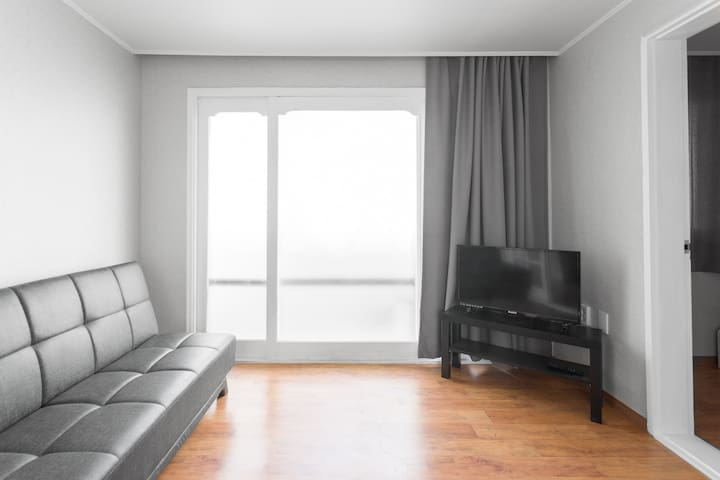 The living room has a fold-down sofa bed and a television. To the right is the small bedroom.