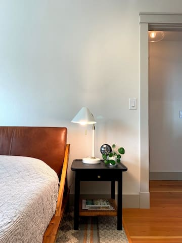Main bedroom furnished with king sized bed, side tables, mounted flatscreen TV and full-length mirror. Empty walk-in closet available for guests to use. Windows face south and east toward the mountain and valley views.
