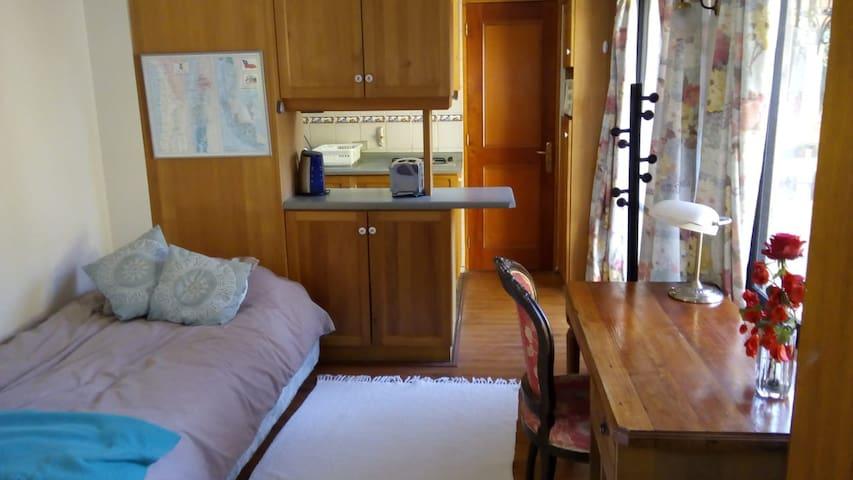 Sala de estar con cama individual y escritorio