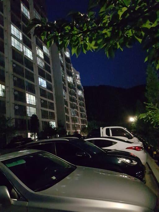 아파트 동 앞/뒤로 넉넉한 주차 공간이 있습니다. with a parking lot