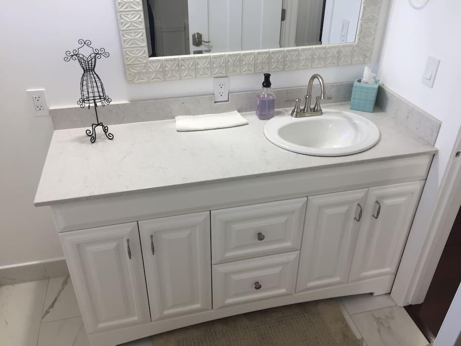 Quartz bath countertop/spash, new cabinet, and new porcelain tile.