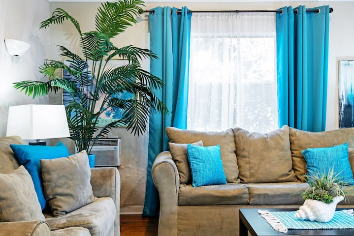 Living room with queen sofa sleeper, high ceilings, hardwood floors & wall unit air conditioner.