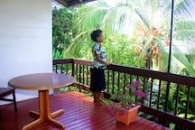 The balcony overlooks lush gardens