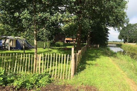 Tent in de boomgaard aan het water - Ruinen