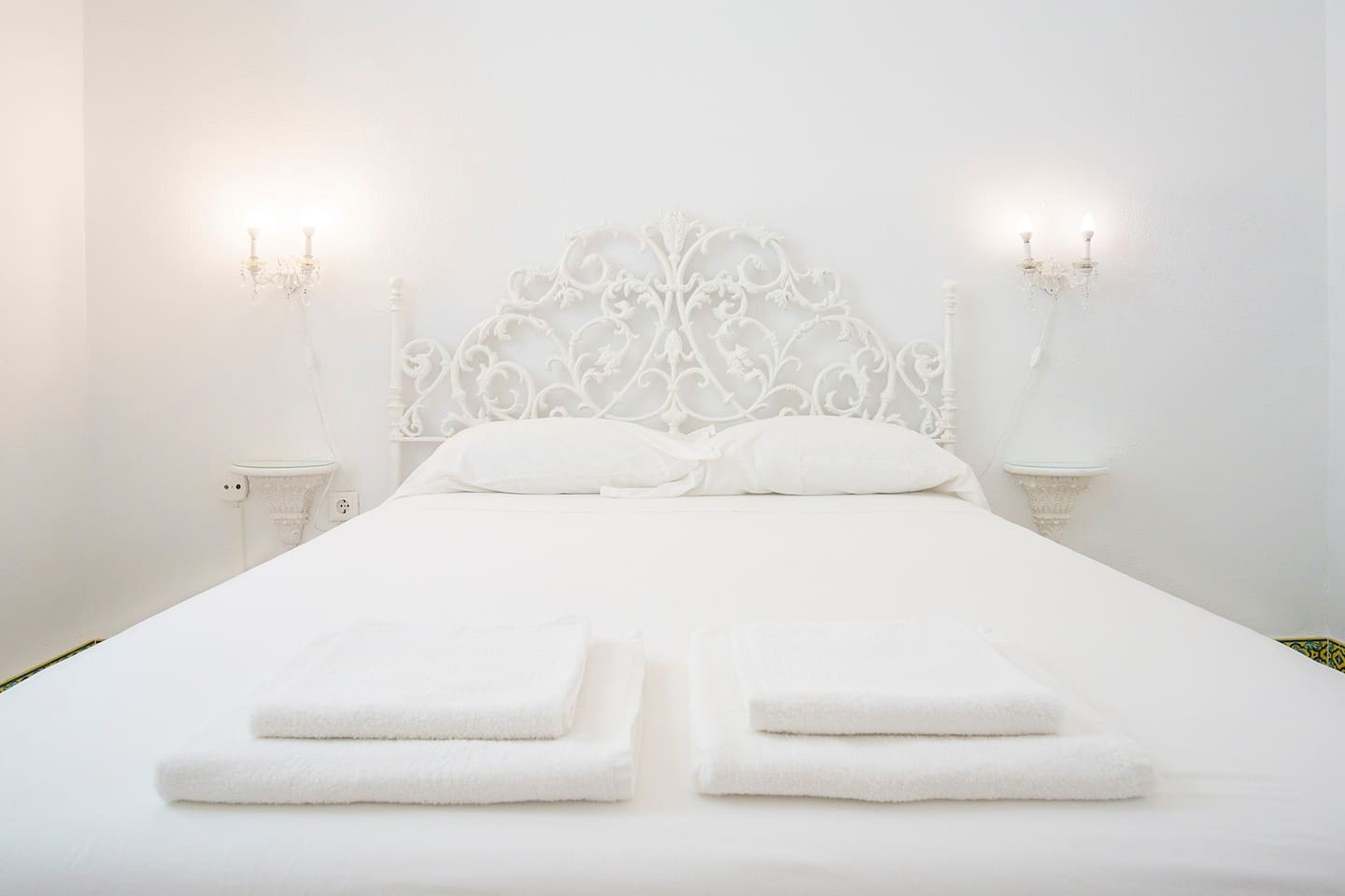 The bedroom has 11m2, a queen size bed, a closet and a coquette with a white marble top. Painted in white and with high ceilings. Triple glazing, stained glass windows and solid wood shutters give access to a balcony overlooking Antonio Lopez Street. Softly illuminated by an old votive lamp suspended from the ceiling and light fixtures on two carved brackets that serve as bedside tables. Towels & linen are provided.