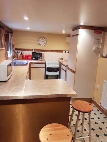 Well equipped kitchen including fridge, washing machine, microwave, toaster, kettle and oven.