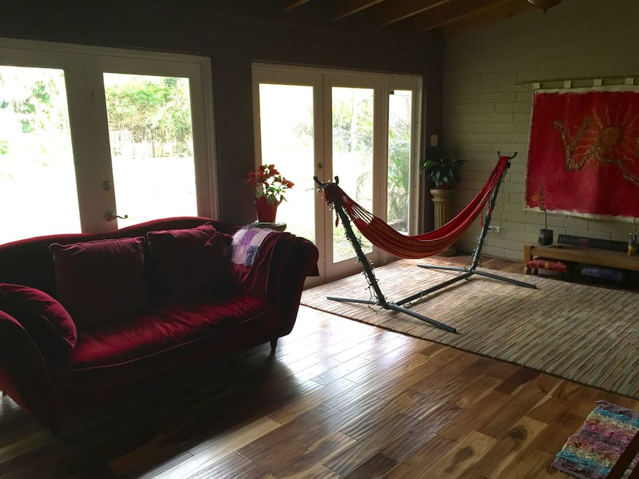 Peaceful entryway and hangout spot, with burgundy velvet couch and indoor hammock. Great place to read, chat, nap or meditate. :-)
