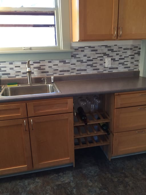 The kitchen is totally updated with a built in wine rack furnished with wine glasses. A four piece place setting, silverware, glasses, cookware and accessories are ready for you to use.