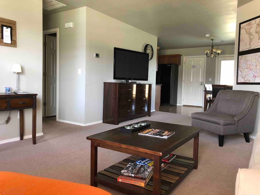 "Living Area with couch, tables, two chairs and a 50"" TV with premium channels."