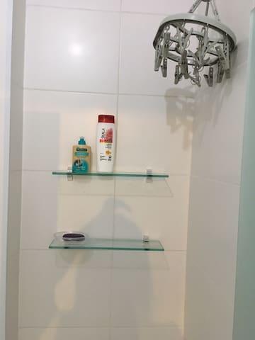 Amplo box, chuveiro elétrico e varal para roupas íntimas e de banho.