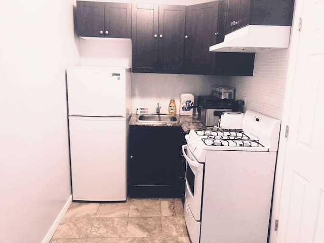 Full kitchen with a 4 burner stove/oven, sink, fridge, deep fryer, toaster, microwave and lots of cabinet space.