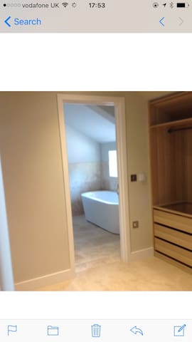 Master dressing room through to en suite bathroom, with separate shower.