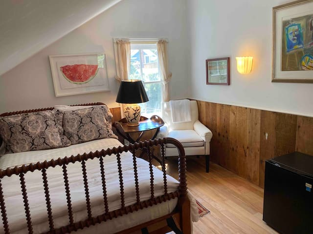 2nd Bedroom with antique bed and original fine art with small refrigerator and view of the sculpture garden.  Separate entry to large shared bathroom.