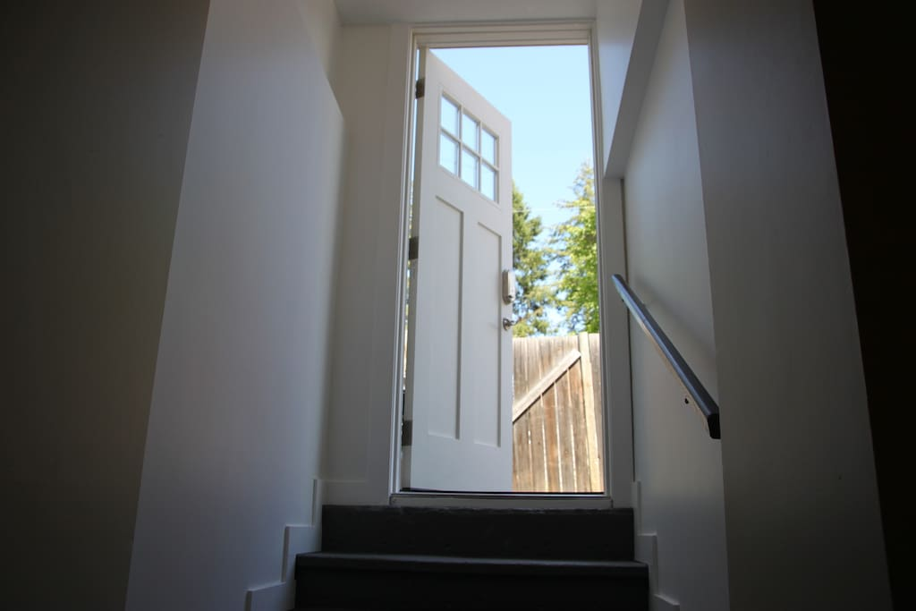 Entrance door to outside private patio with BBQ and these stairs lead down to Living Room