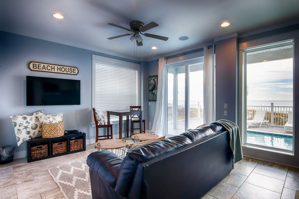 Lower living area with full refrigerator and sink.  Sliding doors lead out to pool area.