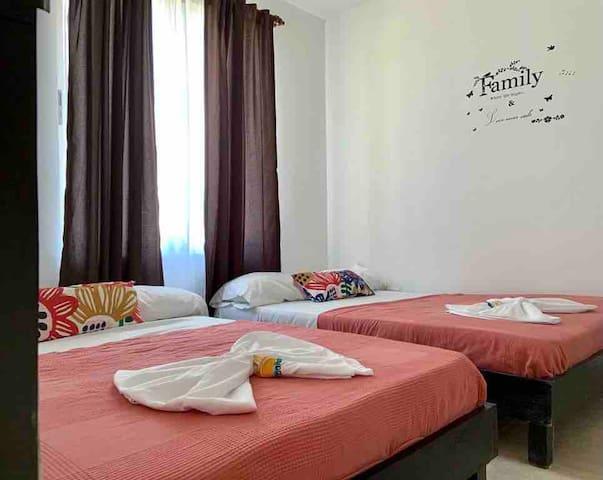 Habitación con dos camas dobles y aire acondicionado