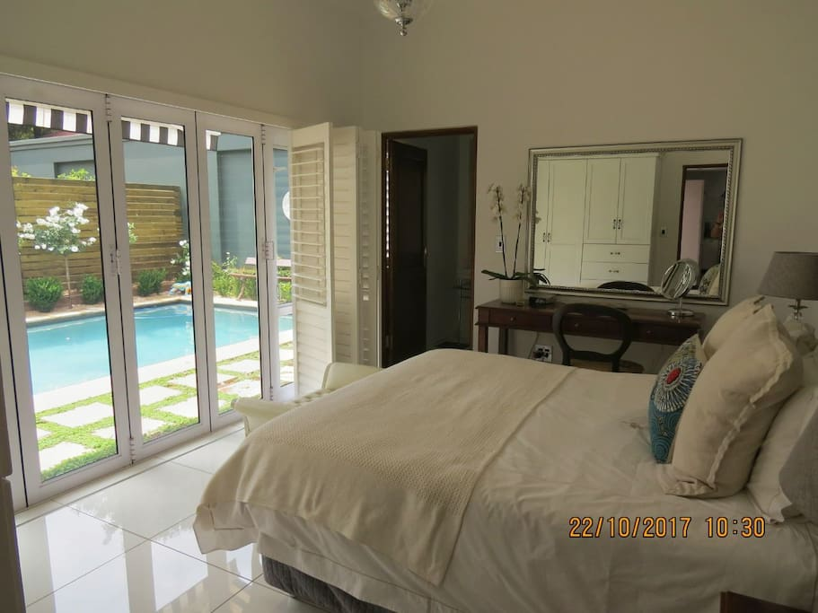 Airy Bedroom 1 Queen bed with en suite bathroom - shower. stacking doors and plantation shutters onto the pool. Sun Awening over the door.