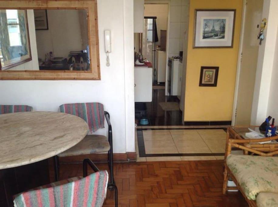 Sala com mesa ampla e sofá. Cozinha americana com todos os objetos para uso.