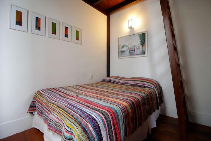 Quarto com cama de casal e acesso ao mezanino para uma pessoa. Room with double bed and access to single mezzannin.