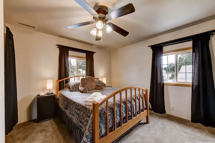 Bedroom with queen bed & ceiling fan.  Windows have room darkening blinds and blackout curtains.