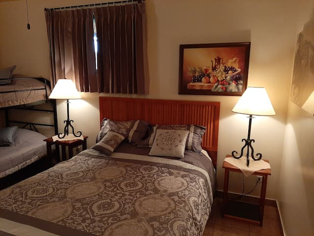 Toucan Room - Sleeps 4. One double bed, one bunk bed. Two entrance doors are provided for emergency escape. One door leads to the kitchen refrigerator where Guest can place items to remain cold. Other door leads to the Guest Terrace and parking area.