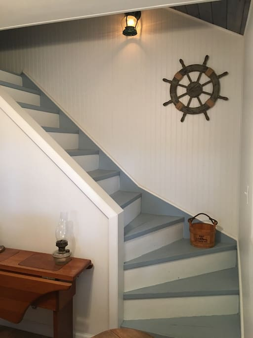 "Stairs in kitchen lead to cute ""boat themed""attic sleeping space geared for  kids."