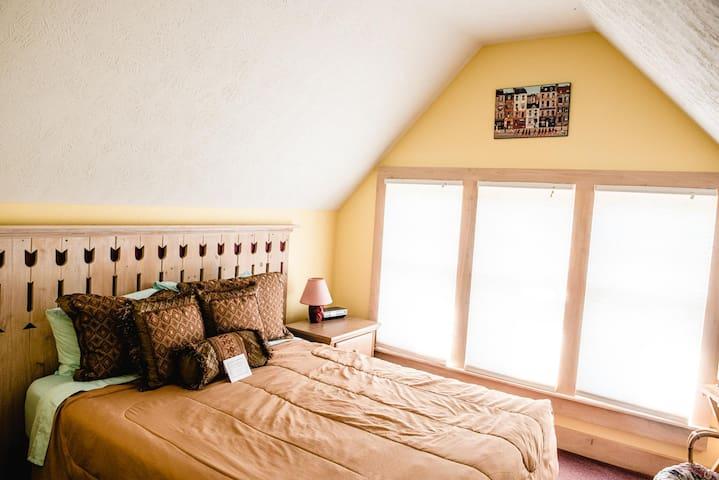 Queen bed with windows overlooking Centennial Park