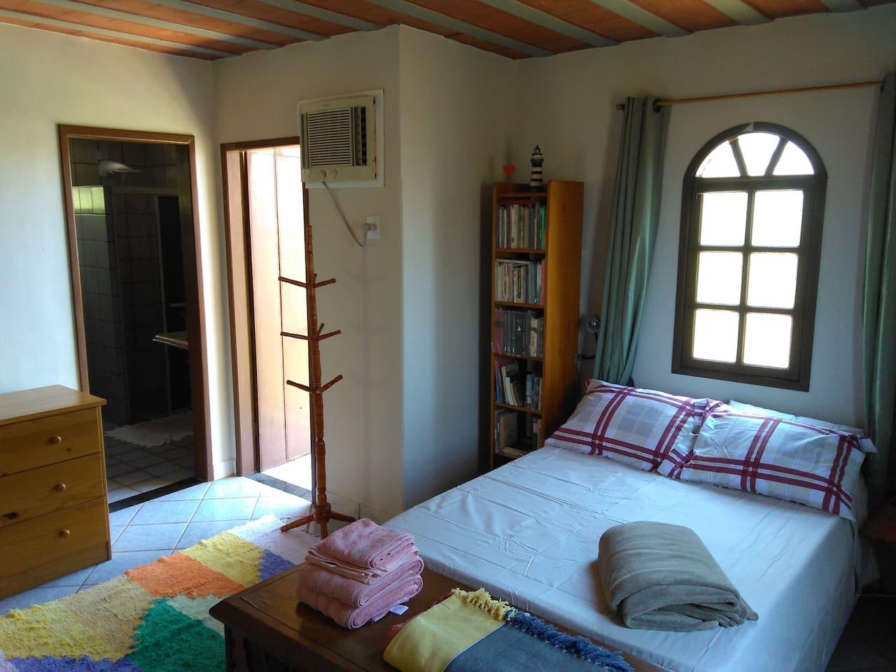 01 Quarto/Suíte Privativa com cama de casal para 02 hóspedes em casa com quintal espaçoso, gramado e cheio de plantas e árvores frutíferas em Meaípe, Guarapari, ES, Brasil.