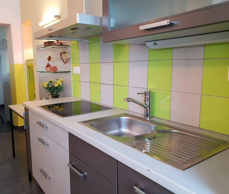 Full kitchen with coffee, tea and fridge.