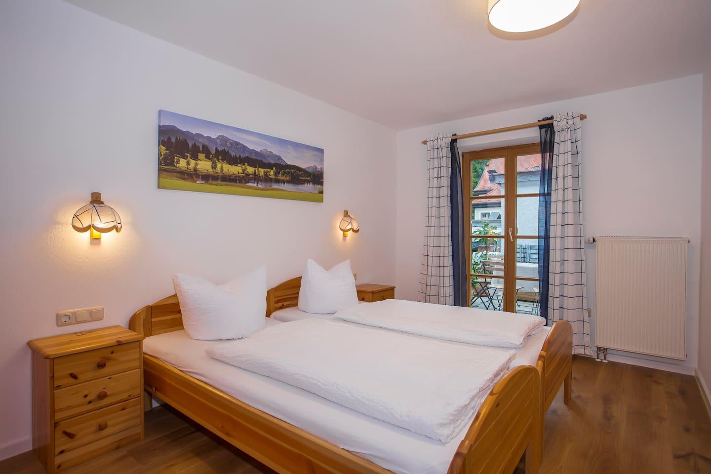 Schlafraum mit zwei Einzelbetten und Zugang zum Außenbereich