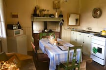 Kitchen with mini fridge, microwave, kettle, toaster, electric stove and wood stove