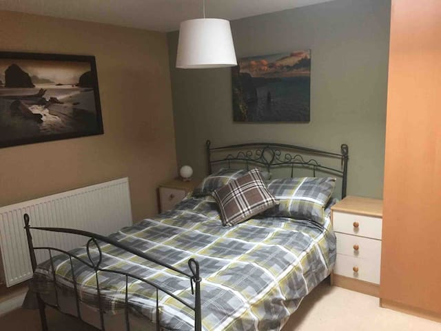 1st bedroom with a double bed and smart tv