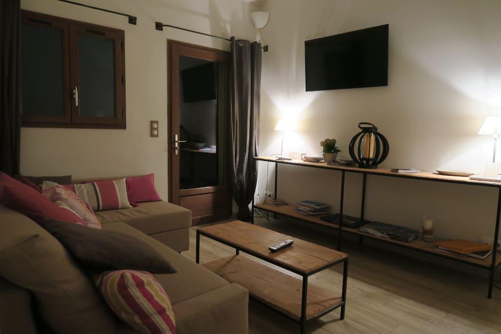 Le salon avec la télévision à écran plat, et sa chaine hifi