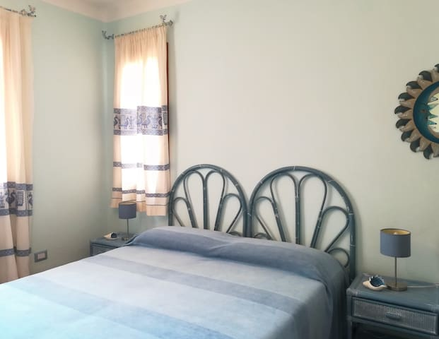 Bright bedroom with single or double beds and Sardinian curtains