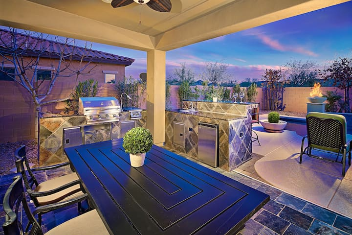 Covered outdoor patio with BBQ and dining table.