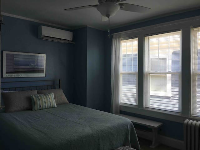 Middle bedroom with queen bed and ceiling fan.