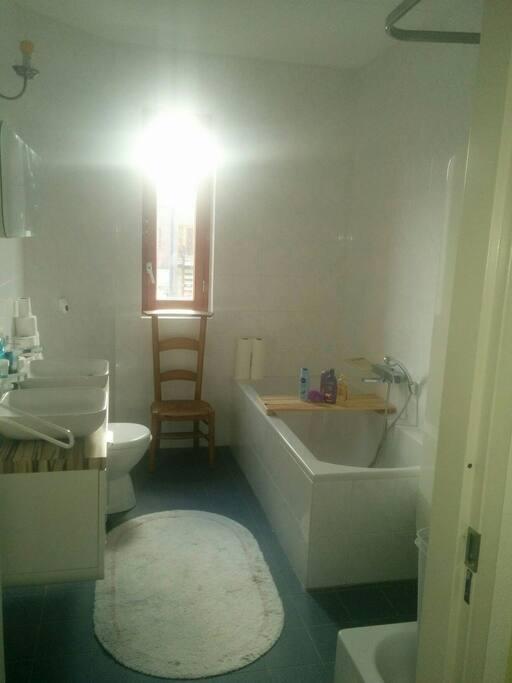 Badkamer met douche wastafel en toilet naast de kamer