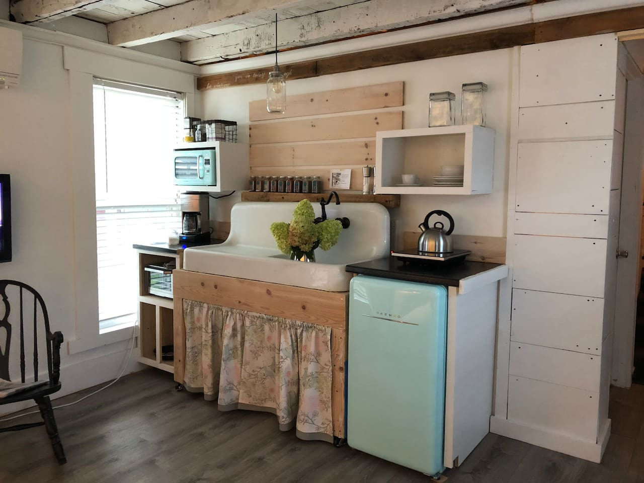 Kitchenette with functional antique farm sink.