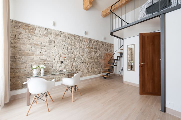 6- wall-bedroom,  living-area with a large table and stairs to the gallery