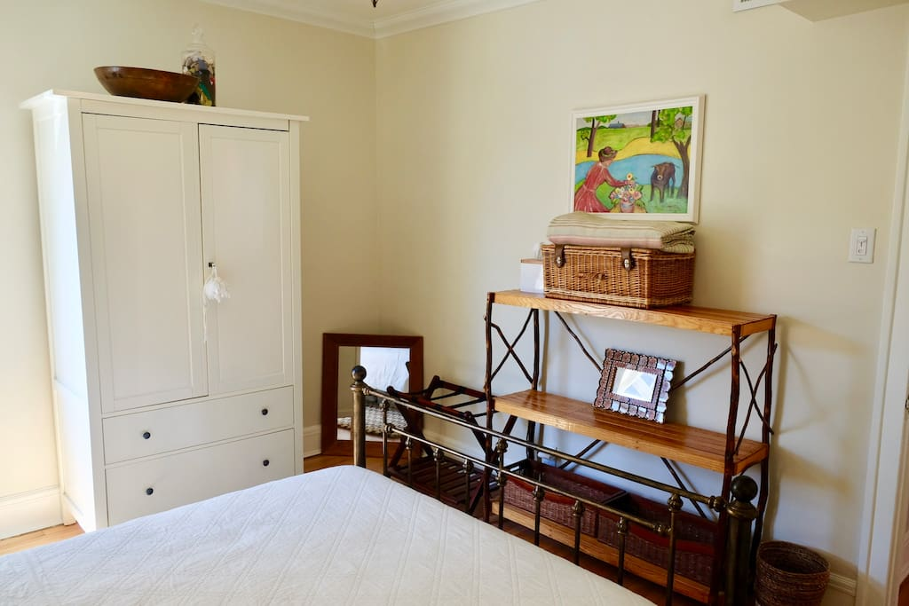 Queen guest bedroom with armoire, luggage rack, and shelving space