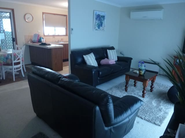 comfy lounge room, large flat screen tv, dvd recorder, dvd's, gas heater, split air con, books and reading lamp