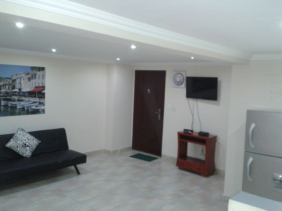 Living area with comfortable sofa, airconditioning and 32 inch Smart TV