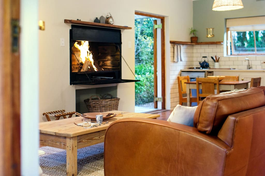 The living space fitted with a comfortable leather coach and fireplace.