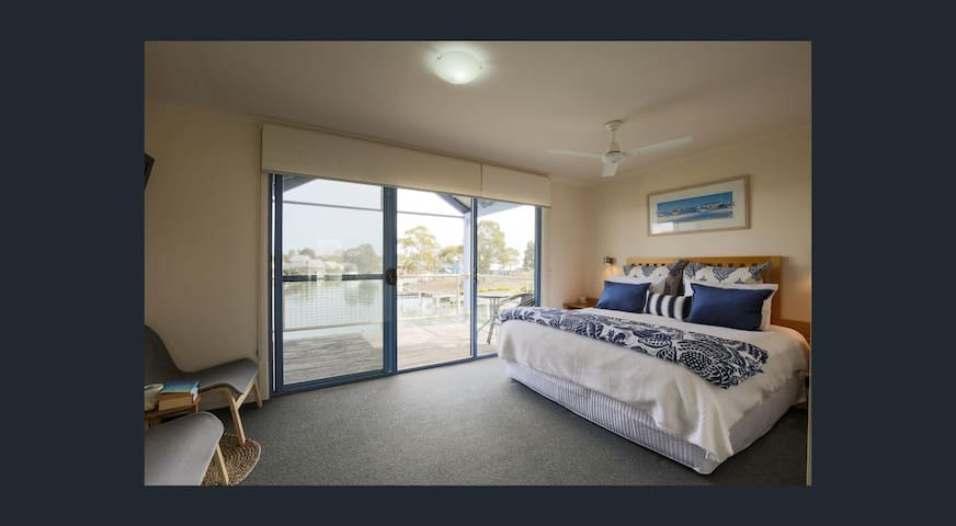 King bed upstairs with balcony overlooking the water.
