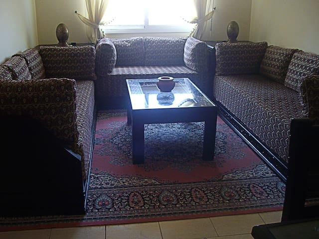 le salon avec deux canapés marocains d'appoint. Table basse